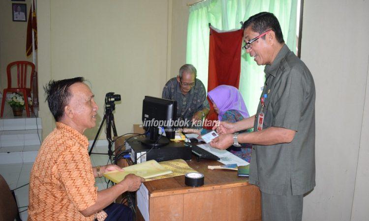 Kepala Disdukcapil Kaltara Samuel Parrangan saat melayani salah seorang warga yang memanfaatkan program Si Pelandukilat,